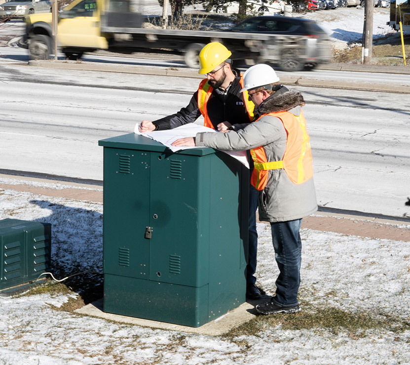 Men on job site looking at blueprints on a green electrical box - DTS Technical